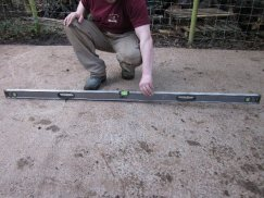 Concrete Base Installer checking levels